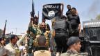 Irakische Soldaten halten eine erbeutete Flagge der ISIS in die Höhe.