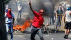 Ein Palästinenser wirft einen Stein bei Zusammenstössen mit der israelischen Polizei in der Nähe von Ost-Jerusalem am  4. Juli 2014.
