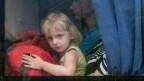 Ein Mädchen schaut aus einem Busfenster, während es mit seinen Eltern die Stadt Slovyansk in der Ostukraine verlässt.
