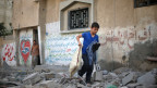 Ein palästinensischer Junge trägt seine Habseligkeiten aus den Trümmern eines Hauses, welches bei einem israelischen Luftangriff in Gaza-Stadt am 15. Juli 2014 zerstört wurde.