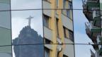 Die Christus-Statue spiegelt sich in der Glasfassade eines Gebäudes in Rio de Janeiro.