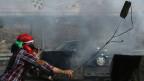 Ein maskierter palästinensischer Demonstrant wirft Steine auf israelische Soldaten während einer Protestaktion gegen die israelische Offensive im Gazastreifen am 18. Juli.