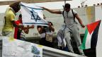 Pro-palästinensische Demonstranten in Paris setzen eine israelische Flagge in Brand.