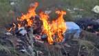 Brennende Wrackteile des abgestürzten malaysischen Passagierflugzeuges MH 17.