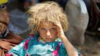 Ein jesidisches Mädchen an der Grenze zwischen Irak und Syrien. Viele Jesiden waren vor den IS-Terroristen ins nordirakische Sinjar-Gebirge geflohen, wo sie zu verdursten und zu verhungern drohten.  Die  kurdischen Milizen haben dann mit Hilfe der USA den Weg zum Tibris freigemacht. Dort gibt es inzwischen provisorische Flüchtlingsunterkünfte.