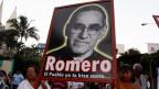 Menschen tragen ein Schild mit einem Bild von Erzbischof Oscar Romero während einer Gedenkfeier in San Salvador.