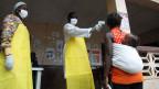 Eine liberianische Krankenschwester misst die Temperatur einer Liberianerin in Bomi County, Liberia.