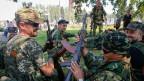 Pro-russische Separatisten mit ihren Waffen nach einer Kundgebung in Donezk.