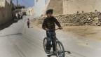 Junge fährt Velo in syrischer Kleinstadt.