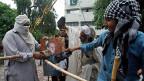 Protestierende in Islamabad treten ihren Präsidenten symbolisch mit Füssen; sie schlagen mit ihren Schuhen auf ein Portrait von Nawaz Sharif ein.