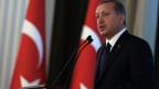 Der türkische Präsident Erdogan am Rednerpult, im Hintergrund eine unscharfe türkische Flagge.
