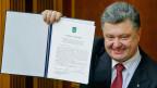 Der ukrainische Präsident Petro Poroschenko mit dem unterzeichneten Assoziierungsabkommen zwischen der Ukraine und der EU.