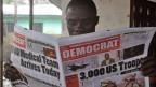 Ein Schwarzer liest eine Zeitung mit der Schlagzeile: 3000 Soldaten aus den USA kommen.