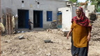 Frauen räumen nach der drei Meter hohen Flut ihre Backsteinhäuser auf.
