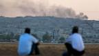 Zwei Kurden schauen von Suruc aus über die Grenze auf die kurdisch-syrische Stadt Kobane.