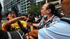 Ein Mitglied der Demokratiebewegung wird von einem Mann angegriffen, der mit den Zielen der «Occupy Central»-Bewegung nicht einverstanden ist.