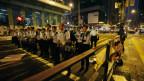 Polizisten stehen in einer Reihe und marschieren in Richtung Demonstranten.