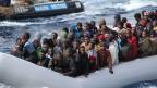 Migranten in einem Boot während einer Rettungsaktion von der italienischen Marine vor der Küste vor der Insel Sizilien.