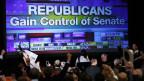 Republikanische Unterstützer jubeln vor einem riesigen TV-Bildschirm, der die positiven Ergebnisse zeigt.