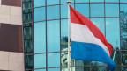 Die Luxemburgische Nationalflagge vor dem Hauptsitz der Bank von Luxemburg.