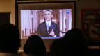 Eine Gruppe von Einwanderern verfolgt Obamas Rede am Fernsehen.