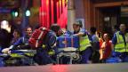 Nachdem die Polizei das Lindt-Café in Sydney gestürmt hat, werden die Geiseln von Rettungskräften geborgen.