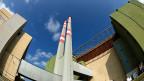 Atomkraftwerk Paks. An einer weiten Schleife der Donau stehen vier riesige Reaktorgebäude,  dazwischen zwei mal zwei schmale hohe Kamine. Bild: Der Reaktor Nummer 4.
