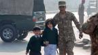 Ein Soldat in Peschawar begleitet einen Schüler und eine Schülerin, nachdem die pakistanische Armee die von Taliban besetzte Schule gestürmt hat.