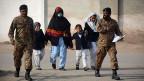 Schulkinder werden von Sicherheitskräften aus der Schule in Peschawar begleitet.