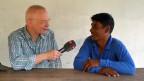 SRF-Südostasienkorrespondent Urs Morf mit dem Fischer Pi Dam - an seinem Esstisch vor dem Haus, das die Deza gebaut hat.