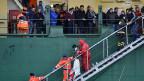Passagiere der in Brand geratenen Adria-Fähre «Norman Atlantic» werden in der italienischen Hafenstadt Bari von einem Schiff geleitet.