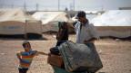Flüchtlinge aus Syrien vor einem Lager an der jordanisch-syrischen Grenze.