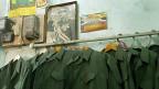 Irakische Armeeuniformen hängen an einer Kleiderstange unter dem Bild von Saddam Hussein, dem ehemaligen irakischen Diktator. Kommen sie zu neuen Ehren? Ein Bild vom Februar 2003.