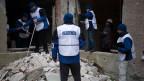 Unbewaffnete OSZE-Beobachter untersuchen ein bombardiertes Gebäude in der Ost-Ukraine.