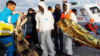Einige Flüchtlinge, die überlebt haben, werden bei der Ankunft im Hafen von Lampedusa von Helfern betreut.