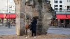 Überrest der zerstörten Frauenkirche in Dresden. Im Gedenken an die Zerstörung der Stadt im Zweiten Weltkrieg zündet diese Frau eine Kerze an.