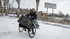 Die Zivilbevölkerung in der Ostukraine ringt Tag für Tag um Strom, Benzin, Wasser und Medikamente. Bild: Mit dem Fahrrad unterwegs in Vuglegirsk, einem Dorf in der Nähe der umkämpften Stadt Debalzewo.