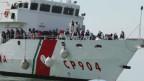 Gerettete Flüchtlinge stehen an Deck eines Bootes der italienischen Küstenwache.