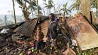 Nach dem Zyklon «Pam» mit dem Leben davon gekommen: Ein Vater mit seinem Sohn vor dem zerstörten Heim in Port Vila, der Hauptstadt der Insel Vanuatu.