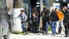 Sicherheitskräfte begleiten Besucherinnen und Besucher des Baro-Nationalmuseums in Tunis  aus der Gefahrenzone.