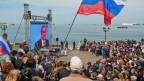 Menschen auf der Krim verfolgen eine Fernsehsendung mit dem russischen Präsidenten Wladimir Putin an der Strandpromenade in Sewastopol, Krim, am 17. April 2014.