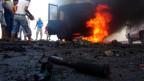Jemeniten versammeln sich bei einem brennenden Auto der Huthi-Rebellen in der Hafenstadt Aden