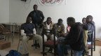 Flüchtlinge aus Schwarzafrika sitzen um einen Tisch in einem karg eingerichteten Raum