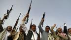 Bewaffnete Anhänger der Huthi mit erhobenen Waffen - nach einem Angriff der saudischen Luftwaffe in der jemenitischen Hauptstadt Sanaa.
