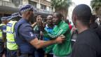 Polizisten versuchen in Durban, Südafrika, demonstrierende Männer zu beruhigen.
