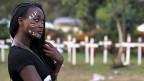 «RIP», Rest In Peace, steht auf der Stirn einer kenianischen Studentin. Sie posiert vor zahlreichen weissen Gedenkkreuzen für die ermordeten Studenten von Garissa.