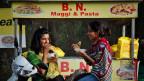 Indische Mädchen essen Nudeln in Ahmadabad, Indien. Die Maggi-Instant-Nudeln sind in Indien ungemein beliebt.