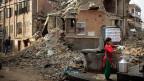 Trinkwasser holen inmitten von Trümmern. Eine Nepalesin in der Hauptstadt Kathmandu.