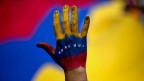 Mit den Farben Vennezuelas die Unterstützung für die Opposition demonstrieren.