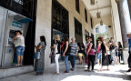 Griechinnen und Griechen in Thessaloniki versuchen an einem Automaten Geld abzuheben
